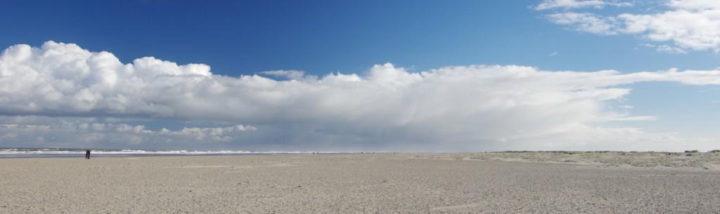 Sandige Fläche, am Horizon ist Brandung zu erahnen. Komplex geformte Wolken stehen vor einem sonst klaren Himmel.